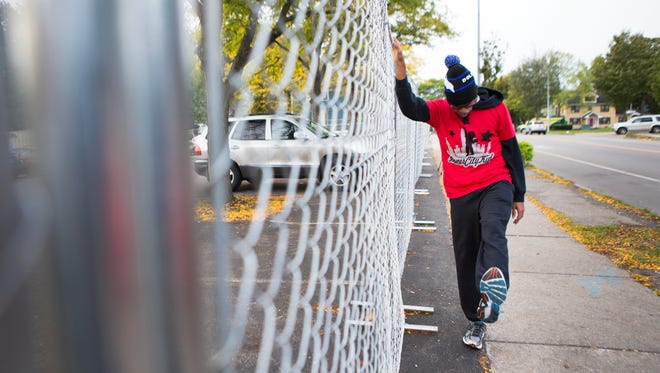 Micah Kalani Johnson stretches along a fence outside of the Boys and Girls Club before beginning his run to New York City on Friday, October 2, 2015. He is running in honor of the young men killed in the shooting outside of the Boys and Girls Club in August.