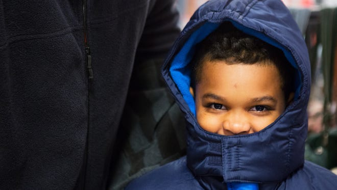 Romeo Gaines, 8, bundles up in his new coat after getting it through the Salvation Army's Project Bundle Up on Saturday.
