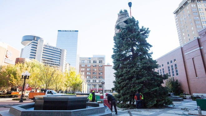 Workers position the Christmas tree for this years celebration in downtown.