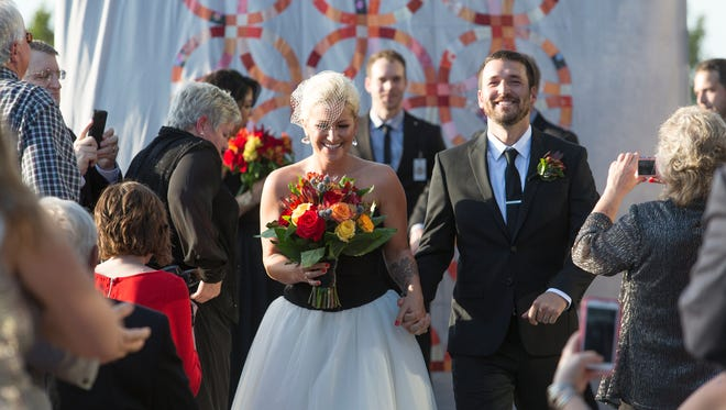 Jackie Zykan and her groom, Adam Breitenstein walk down the aisle as husband and wife.