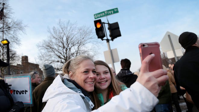 Rebecca Dostie, left, 42, of Royal Oak takes a selfie with Madison Gibson, 11, of Royal Oak during the unveiling of the new Glenn Frey Drive on Thursday, February 18, 2016, in Royal Oak intersecting North Washington Avenue and North West Street that will run adjacent to Royal Oak Middle School.