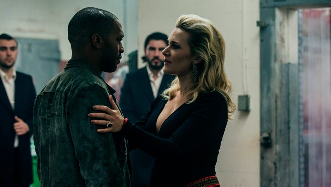 """Chiwetel Ejiofor faces off with Kate Winslet) in """"Triple 9."""""""