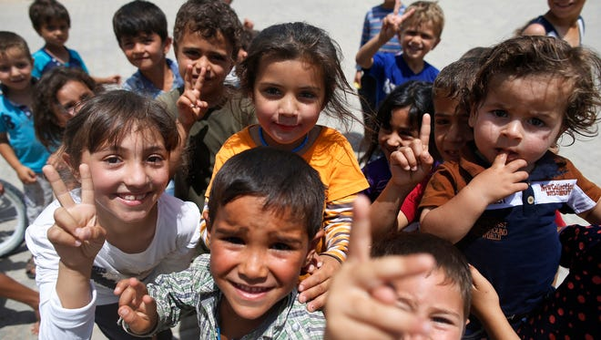 Syrian refugee children flash peace signs at the Oncupinar camp in Turkey near the Syrian border in June.