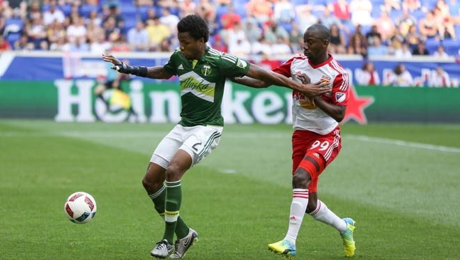 Portland Timbers' Alvas Powell, left, defends the ball from New York Red Bulls' Bradley Wright-Phillips, right, during the first half of an MLS soccer match, Sunday, July 10, 2016, in Harrison, N.J.