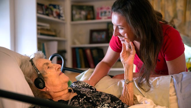 Kerry Morris, 24, one of 92-year-old Margaret Coleman's 48 grandchildren, visits with her at the Coleman family home Monday, July 25 in Chicago. Although she is on oxygen and can no longer walk, Margaret remains in high spirits and wishes to stay in the family house, so her children organize and take turns caring for her during the week. She also receives frequent visits from many of her 48 grandchildren and 13 great-grandchildren. (Erin Hooley/Chicago Tribune/TNS)