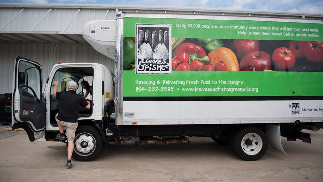 Loaves and Fishes driver Randy Allen hops on the truck to head to the next delivery site on Tuesday, August 23, 2016. Steve White Volkswagen will be collecting food for Loaves and Fishes this weekend.