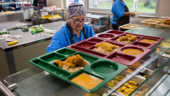 Joyce Wessel, left, and Gabriela Perez-Flores prepare meals during lunch time at Meredith Middle School in Des Moines in this file photo.