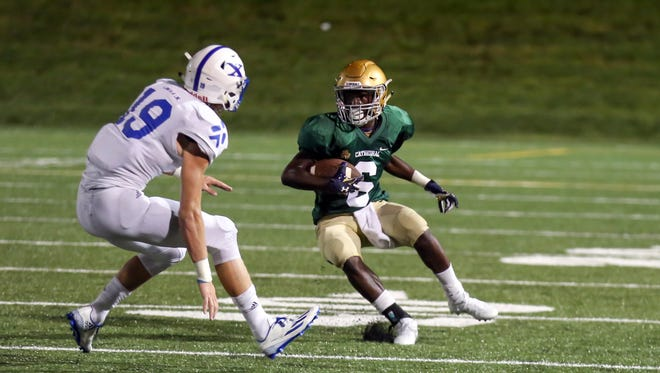 Cathedral's Daijon Collins looks for running room against St. Xavier at the Butler Bowl on Friday night.