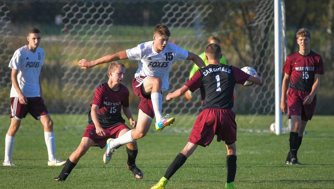 Derek Schoeni (15) of Omro kicks the ball away from Ethan Feucht (1) and Ryan Batterman (15) of Mayville.   The Omro Foxes hosted the Mayville Cardinals Tuesday afternoon in soccer.