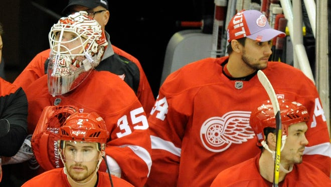 Red Wings goalie Jimmy Howard (35) and goalie Petr Mrazek (34) watch their team play against the Panthers in the final minute in the third period of the Wings' 5-2 loss Sunday at Joe Louis Arena.