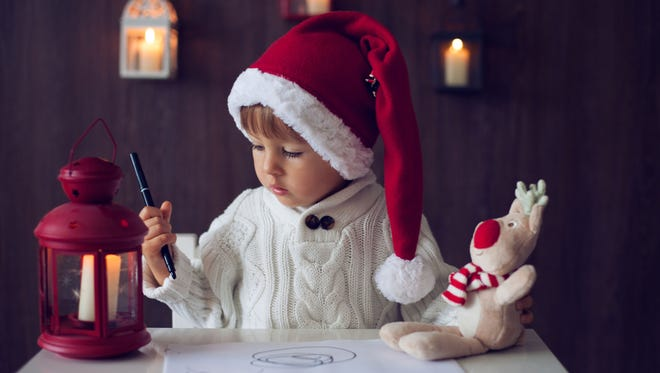 Boy, writing letter to Santa with his friend.