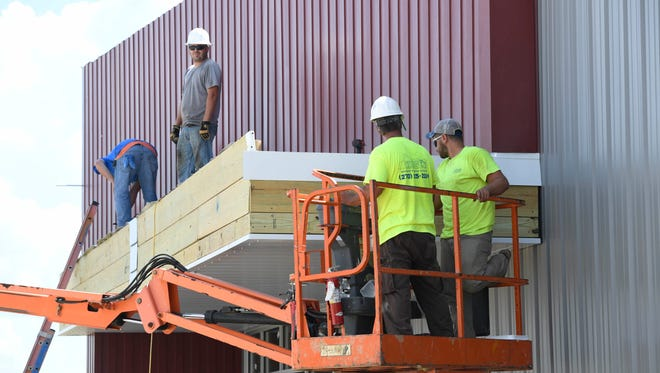 Construction workers build on the new Vanderburgh County Sheriff's command building under construction next to the administration office on N. Harlan Avenue Tuesday, June 13, 2017.
