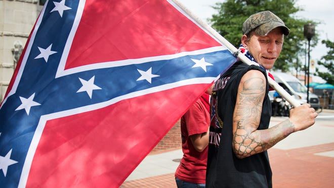 John Garrett looks back at the Confederate flag he is carrying on the corner of S Main and Broad Streets on Sunday, August 13, 2017. People with the flags showed up following a Stand Against White Supremacy rally that was held outside of the Peace Center.