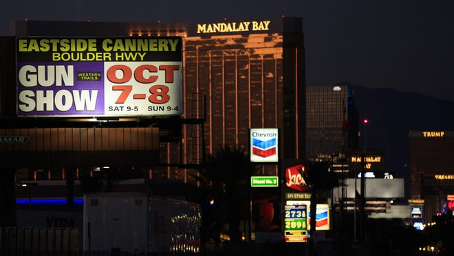 With the Mandalay Bay Resort and Casino in the background, a billboard advertising an upcoming gun show is seen Oct. 3, 2017, along the Las Vegas Strip in Las Vegas, Nev. The advertised show later was canceled.