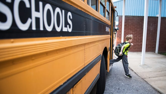 A student gets off the bus at Fork Shoals Elementary on Tuesday, November 14, 2017.