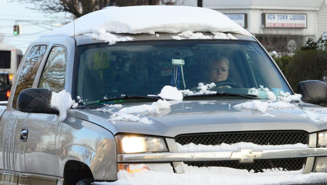 A woman drives her pickup truck March 15, 2017, in East Rutherford, N.J., without clearing the snow from its roof.