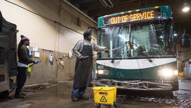 Porenza Hailstock washes a Greenlink bus on Monday, February 5, 2018.