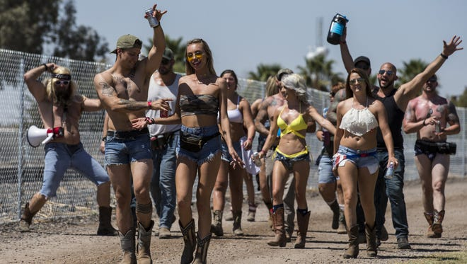 Festival-goers walk near the campgrounds during Day 1 of Country Thunder Arizona on Thursday, Apr. 5, 2018 in Florence, Ariz.