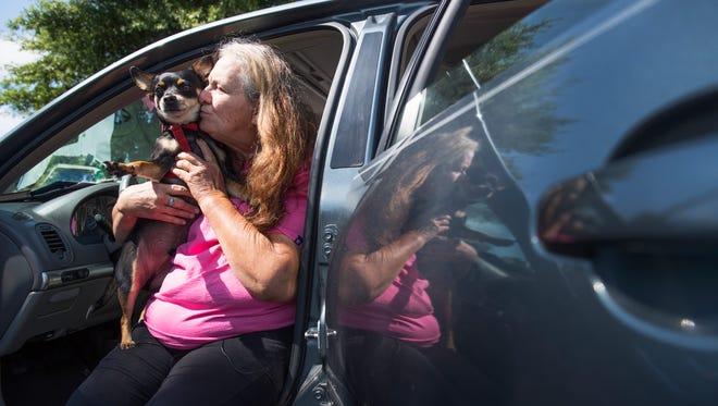 Barbara Keller kisses her dog, Cruz, outside of a Walmart in Taylors on Wednesday, June 13, 2018.