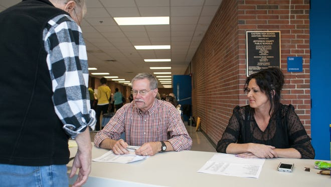 Election officials; Tom Aldred, left, and Melissa Daniels check a voter in at the Eastern High School voting precinct. 'I've seen more voters in their 50's or older voting, but more younger people overall at the election this time around,' Daniels said.Nov., 4, 2014