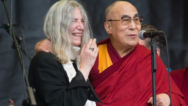 The Dalai Lama speaks to the crowd during singer Patti Smith's, left, performance at the Glastonbury music festival on Sunday, June 28, 2015 at Worthy Farm, Glastonbury, England.
