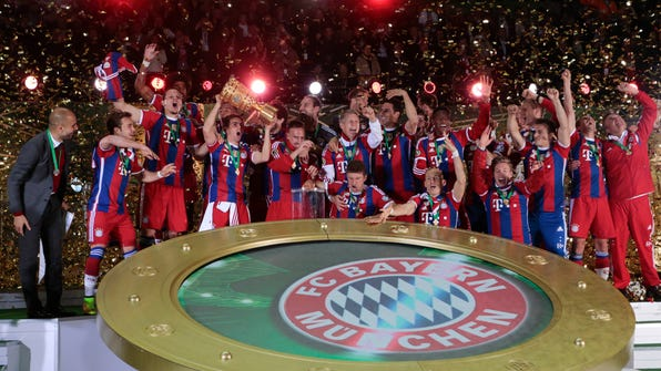 The team of German soccer club Bayern Munich celebrates with the trophy after winning the German Soccer Cup Final between FC Bayern Munich and Borussia Dortmund at the Olympic Stadium Berlin, Germany, Saturday, May 17, 2014. (AP Photo/Markus Schreiber)