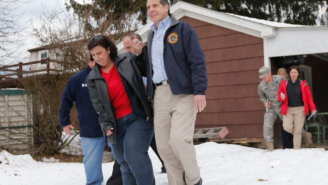 Gov. Andrew Cuomo helps Nancy Barletta through the snow at her house Monday while surveying the aftermath of a lake-effect snowstorm in West Seneca.