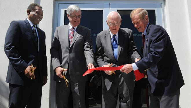Donald Graham (from left), district judge, U.S. District Court; and Frank Lynch Jr., U.S. magistrate judge, stand by as former Fort Pierce Mayor Dr. William Dannahower is assisted by Sen. Bill Nelson, D-Fla., during the ribbon-cutting ceremony for the new federal Courthouse in Fort Pierce in March 2012.