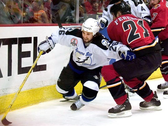 Tampa Bay Lightning's Martin St. Louis is checked during Game 6 of the 2004 Stanley Cup Finals. St. Louis and Tampa won the series in seven games.