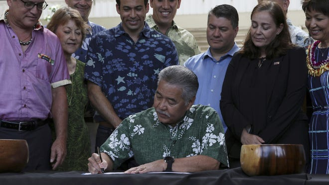Hawaii Gov. David Ige signs legislation banning the sale of sunscreens containing two chemicals believed to harm coral reefs Tuesday, July 3, 2018, in Honolulu. The prohibition takes effect in 2021, but high levels of oxybenzone and octinoxate have already been detected.