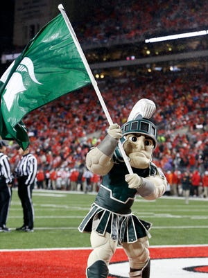 The Michigan State Spartans mascot waves a flag on the field against the Ohio State Buckeyes at Ohio Stadium.