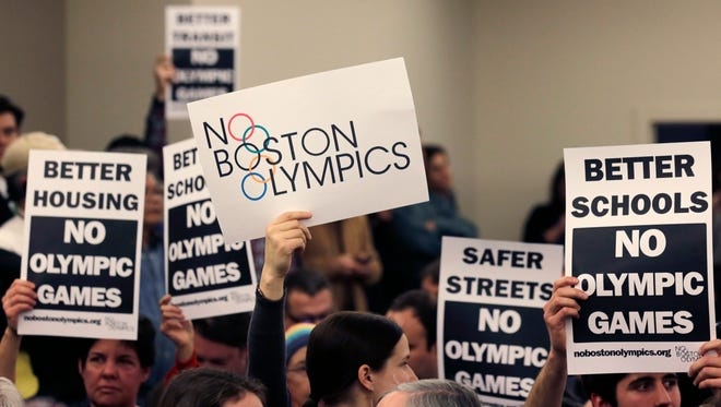 The audience hold up placards against the Olympic Games coming to Boston, during the first public forum regarding the city's 2024 Olympic bid.