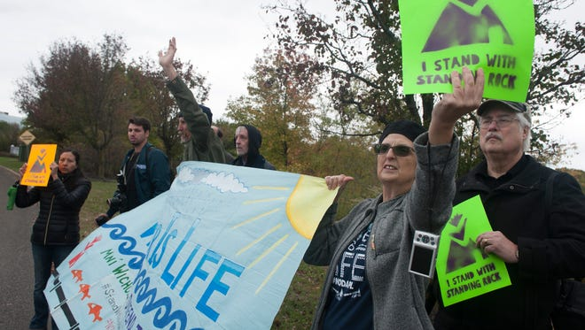 Diane Beeny waves a sign during a pipeline protest outside TD Bank in Mount Laurel.