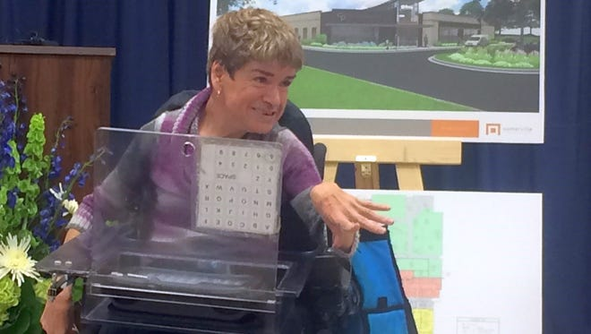 Vicki Nass, who has cerebral palsy and has been a client at the CP Center for 25 years, uses a communication device to convey words of gratitude during an announcement Tuesday for the final fundraising phase of a $7.5 million campaign to expand and renovate the center in Allouez.