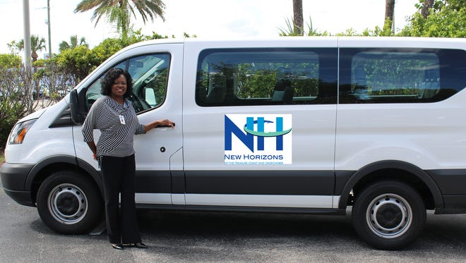 Harley Eady, New Horizons Mental Health's Martin County outpatient clinic manager, stands with the van donated by the Hobe Sound Community Chest.