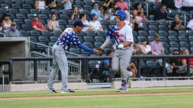 Amarillo Sod Dogs catcher Kurtis Byrne (right) is congratulated by Ken Jarrett after hitting a solo home run in Saturday night's game against the Round Rock Hairy Men at Hodgetown. The Sod Dogs lost 7-6.