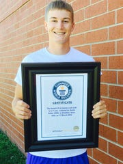 Brooklyn's Austin Keller with his certificate certifying his world record-breaking performance in setting the record for fastest 20-meter human crab walk at BGM.