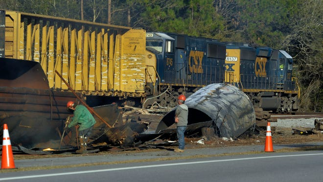 Workers using cutting torches to dismantle the remains of railcars that derailed recently along Highway 90 east of Highway 87 while a train passes by in the background Friday afternoon.
