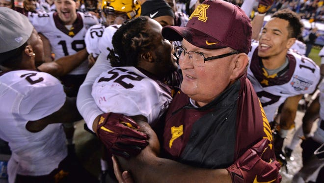 Minnesota coach Tracy Claeys gets a hug from defensive lineman Yoshoub Timms after the team beat Washington State in the Holiday Bowl.