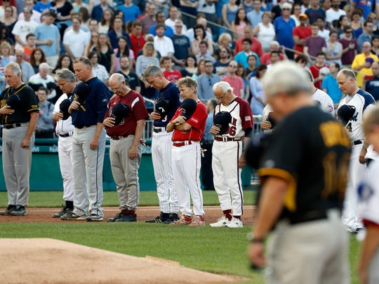 Members of both congressional teams bow their heads for a moment of silence for Rep. Steve Scalise, R-La., before the Congressional baseball game Thursday, June 15, 2017, in Washington. The annual GOP-Democrats baseball game raises money for charity.