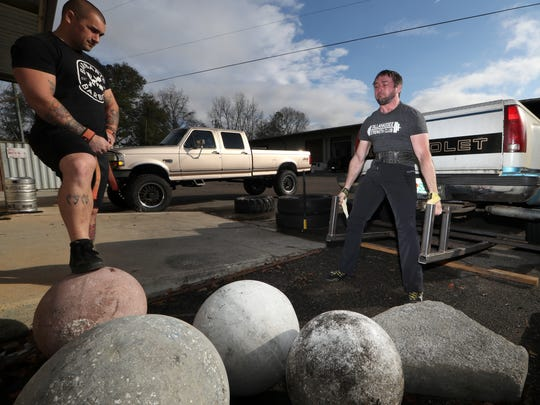 Brett Fain lifts a rear end of a Chevy pickup truck, a weight of more than 750 pounds at Tallahassee Strength Club at Boot Camp Fitness and Training as workout partner Kyle Rojas watches on Feb. 2. Fain placed 7th overall in the 2017 Strongman World Championship in December.