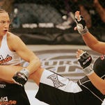 Kaitlin Young, left, fights off a kick by Gina Carano in their EliteXC 140 lbs. bout at the Prudential Center in Newark, N.J. on May 31, 2008.