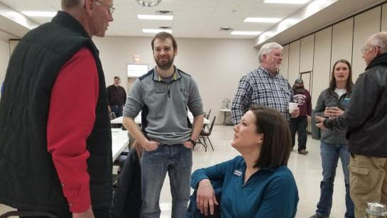 At their annual meeting in February, Hawk Creek staff Jordan Austin (second from left), Heidi Rauenhorst (seated) and Dean Dambroten (behind Heidi) interacted with attendees.