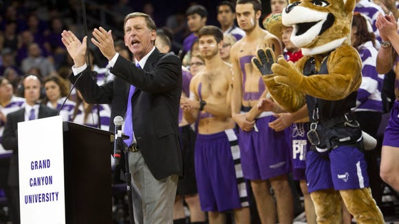 Grand Canyon University CEO Brian Mueller leads students in a cheer for the university basketball team.