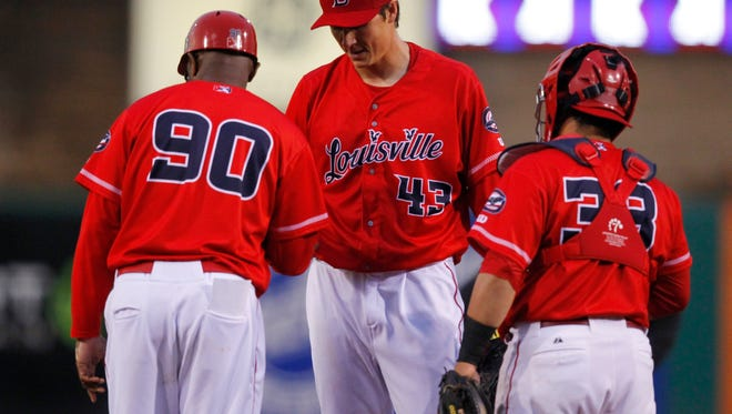 Louisville Bats pitcher Homer Bailey (43) hands the ball off to manager Delino DeShields (90) during the fourth inning of play against the Indianapolis Indians at Louisville Slugger Field in Louisville, Kentucky.         April 21, 2016