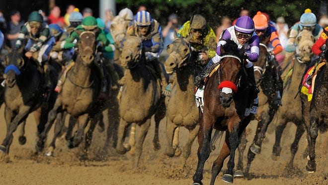 Mario Gutierrez (center) encourages Nyquist as he rounds the fourth turn and races for the win in the 142nd running of the Kentucky Derby on Saturday at Churchill Downs. May 7, 2016. Photo by David Lee Hartlage, Special to the Courier-Journal.