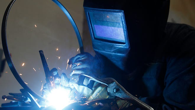 A welder works with the metal tension hoop at the Deering Banjo Company in Spring Valley, Calif. Jan. 9, 2013. (Mark Boster/Los Angeles Times/TNS)