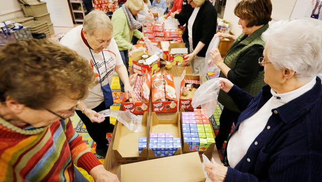 This Nov. 18, 2014, file photo shows volunteers filling bags with food for the Backpack Food Program at Grace United Methodist Church in Sioux City, Iowa,   (AP Photo/The Sioux City Journal, Jim Lee)
