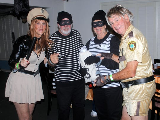 People dressed as police officers from Reno 911 playfully arrest people dressed as bank robbers in this USA Today file photo.