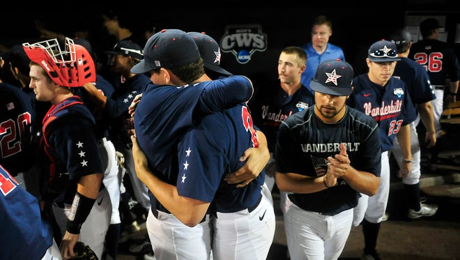 Vanderbilt players Ben Bowden, left, hugs John Kilichowski in the dugout after a 9-8 win over Virginia at the College World Series at TD Ameritrade Park in Omaha, Neb., Monday, June 23, 2014.
